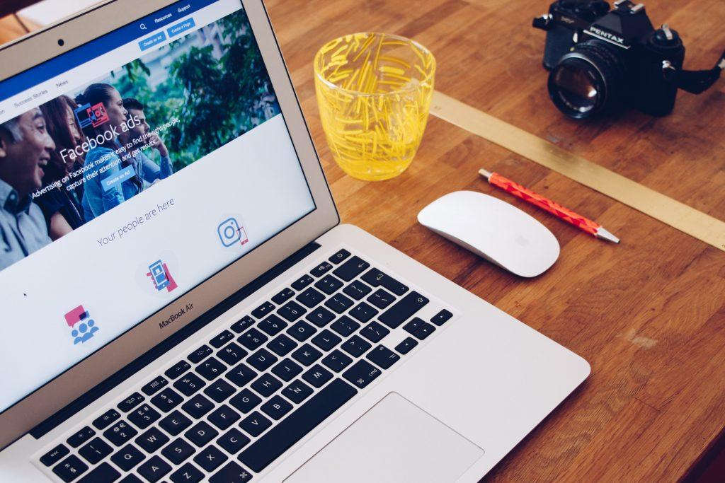 Ordinateur ouvert sur la page de Facebook, placé sur une table