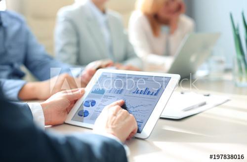 Un homme tiens un Ipad et analyse les données affichées. Marketing internet