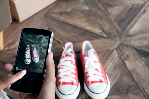 Une personne qui photographie ses souliers pour ensuite les vendre.